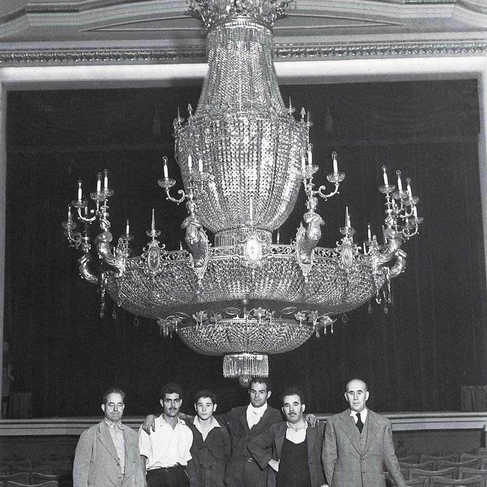 La làmpara al pati de butaques del teatre quan fou penjada en 1952. El primer de la dreta és l'artista que la dissenyà, Enrique Mariner Saurí.